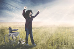 Man gets up from wheelchair on meadow Royalty Free Stock Images