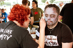 Man Gets Zombie Makeover From Makeup Artist. Atlanta, GA, USA - June 8, 2013: An unidentified man gets a zombie makeover after the Atlanta Zombie Run, a 5K run royalty free stock photography