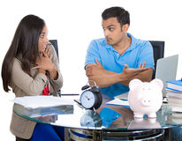 Man getting angry at woman for spending too much money and pointing at bills on laptop Royalty Free Stock Images