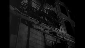 Man getting down from fire escape at night stock footage