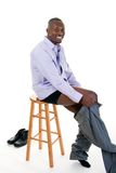 Man Getting Dressed. Handsome African American man in a shirt and tie sitting on a stool and putting on his pants Stock Images