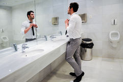 Man getting dressed in a public restroom Stock Photography