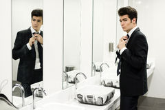 Man getting dressed in a public restroom with mirror Stock Photos