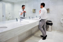 Man getting dressed in a public restroom with mirror Stock Image