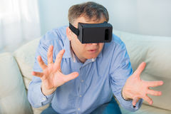 Man getting experience using VR-headset glasses of virtual reality at home Royalty Free Stock Image
