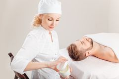 Man is getting face skin treatment. Beautiful cosmetician in medical gloves. Handsome men is getting face skin treatment. Beautiful cosmetician in medical gloves royalty free stock image