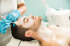 Man getting a facial treatment. Profile view of a young men getting a moisturizing facial treatment in a health spa stock photo