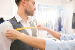Man Getting Fitted for Bespoke Suit in Atelier. Portrait of unrecognizable tailor measuring mature bearded men fitting bespoke suit in traditional atelier studio royalty free stock photo