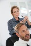 Man getting haircut by woman hairdresser Stock Photos