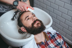 Man getting hairwash by hairdresser in hair salon. Handsome man with beard in checkered shirt getting hairwash by hairdresser in hair salon Stock Image