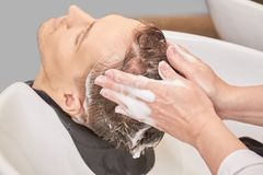 Man getting head washed, shampoo. Hands of female barber. Shampoo reviews and ratings royalty free stock photography