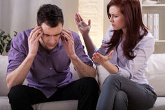 Man getting a headache. In the middle of marital quarrel Royalty Free Stock Photography