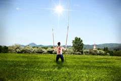 Man is Getting Help from God. Man Standing Alone on Grass Field is Taking a Ropes from Heaven Royalty Free Stock Image