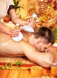 Man getting herbal ball massage treatments . Royalty Free Stock Images