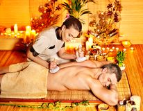 Man getting herbal ball massage treatments . Stock Photography