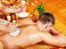 Man getting herbal ball massage treatments . Royalty Free Stock Image