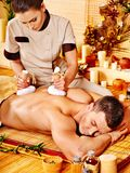 Man getting herbal ball massage treatments . Stock Image