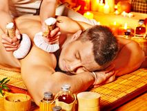 Man getting herbal ball massage treatments . Royalty Free Stock Photography