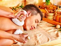 Man getting herbal ball massage treatments . Man getting herbal ball massage treatments in spa royalty free stock image