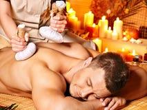 Man getting herbal ball massage treatments . Man getting herbal ball massage treatments in spa stock photos