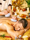Man getting herbal ball massage treatments . Royalty Free Stock Photos