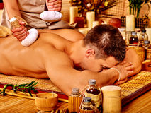 Man getting herbal ball massage treatments Royalty Free Stock Photo
