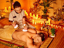 Man getting herbal ball massage treatments Stock Photos