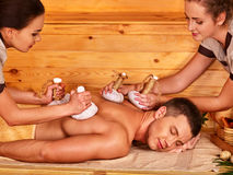 Man getting herbal ball massage treatments. In spa. Two women royalty free stock images