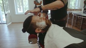 Barber applying shaving cream to client beard stock video