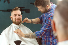 Man getting his beard shaved in a barber shop Stock Photo