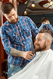 Man getting his beard shaved in a barber shop Stock Photos
