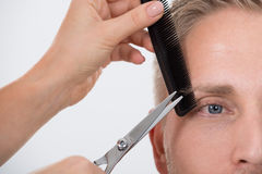 Man Getting His Eyebrow Trimmed Against White Background Stock Images
