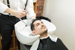 Man Getting His Hair Washed By Barber In Salon. Confident young man getting his hair washed by barber in salon Stock Photography