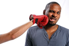 Man Getting Hit on Face. African American man getting hit on face by gloved hand Stock Images