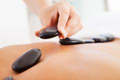 Man getting hot stone massage Stock Image