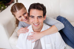 Man getting hugged by his girlfriend on the sofa Stock Images