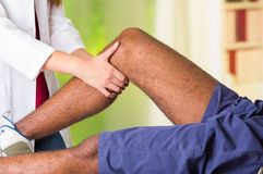 Man getting knee treatment from physio therapist, her hands holding his leg and applying massage, injury medical concept Royalty Free Stock Images