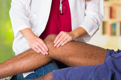 Man getting knee treatment from physio therapist, her hands holding his leg and applying massage, injury medical concept Stock Images