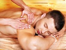 Man getting massage. Man getting massage in woden spa. Female therapist Royalty Free Stock Image