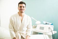 Man getting a massage in a spa. Happy young man sitting on a massage bed and waiting to relax and get pampered at a health spa Royalty Free Stock Photography