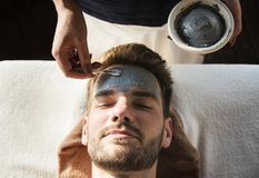 Man getting a mud mask at a spa stock images
