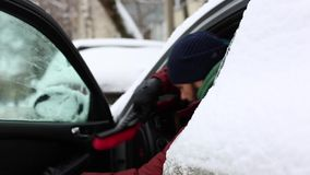 Man getting out of a car on a snowy day - winter traffic.  stock video footage