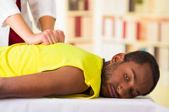 Man getting physical treatment from physio therapist, her hands working on his back and applying massage, medical. Concept Stock Photography
