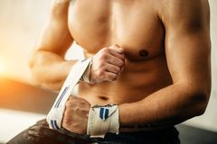 Man getting prepared for the training, wrapping her hands with bandage tape. Fit man getting prepared for the training, wrapping her hands with bandage tape Royalty Free Stock Image