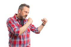 Man getting ready to fight with copyspace. Angry man getting ready to fight with copyspace holding fists isolated on white studio background royalty free stock photography