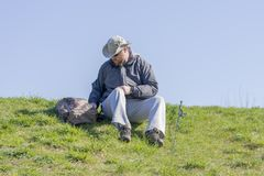 Man getting ready to fish from a grassy riverbank, sitting and l Royalty Free Stock Photo