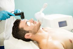 Man getting RF facial in a spa Stock Images