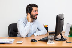 Man getting some good news over the phone. Using headset. Enthusiastic worker talking over the phone using a headset Stock Photography