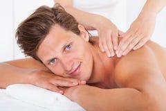 Man getting spa treatment. Shirtless Man Lying On Front Getting Spa Treatment Stock Image