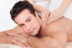 Man getting spa treatment. Shirtless Man Lying On Front Getting Spa Treatment Royalty Free Stock Photo